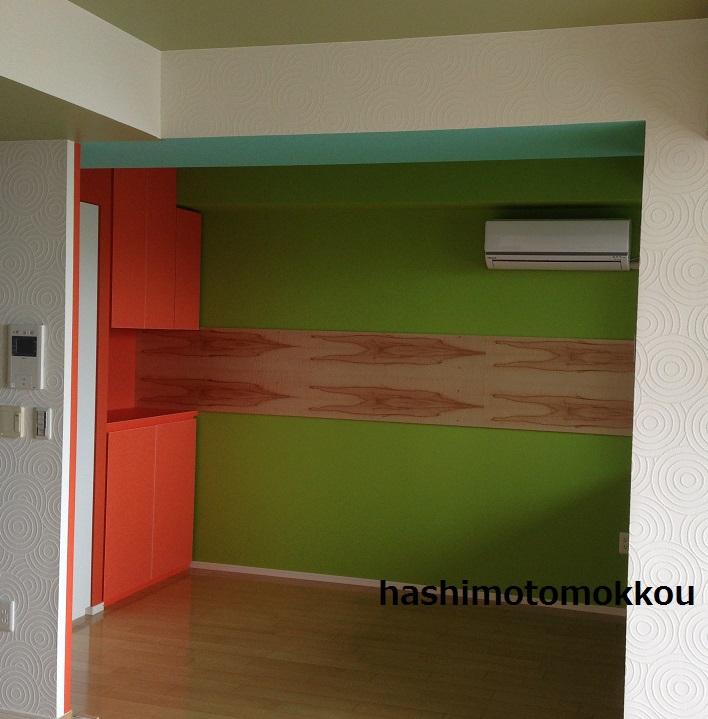 鮮やかなオレンジの収納棚と壁面インテリア